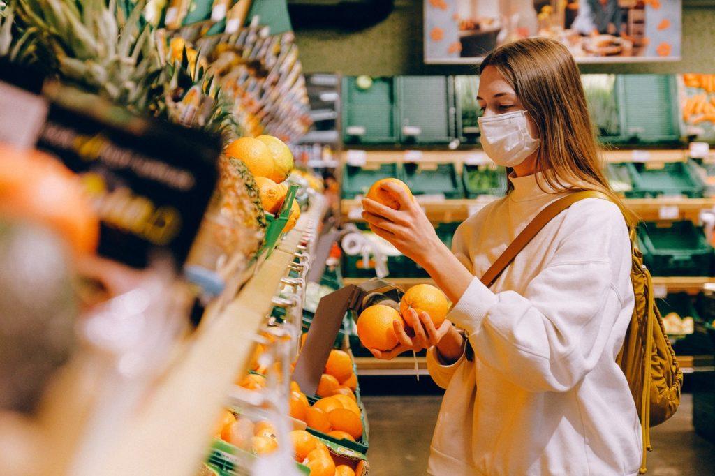 Auxílio em razão dos reflexos da pandemia. Cliente se protege com máscara enquanto faz compras no supermercado.